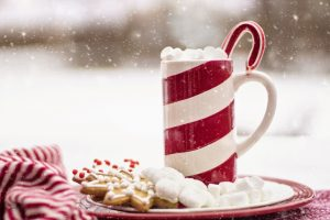 mug with candy cane and a plate of cookies