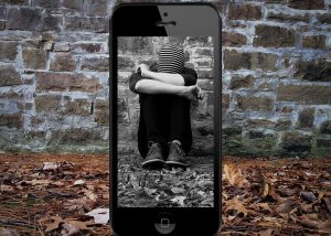teen with head down sitting against a wall. Framed in a cell phone screen.